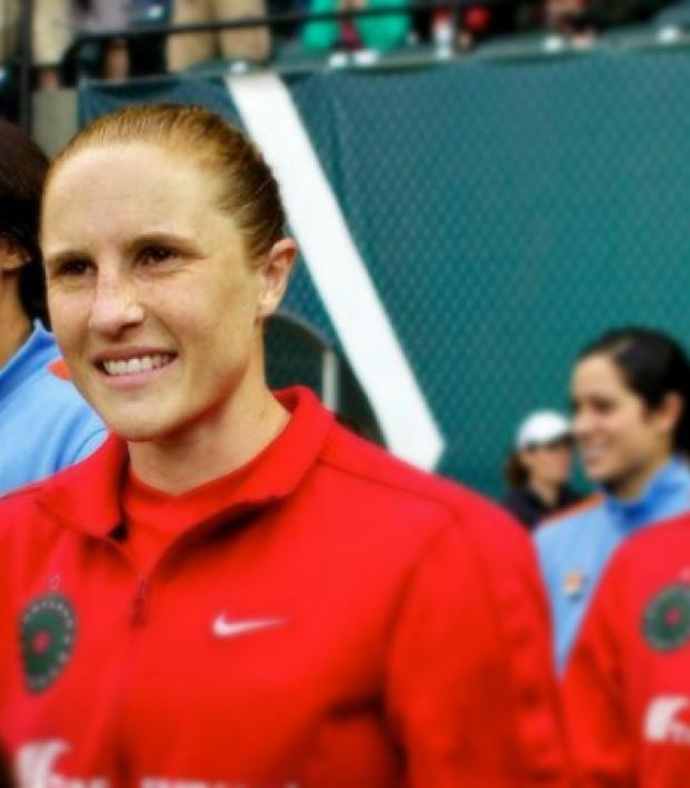Rachel Buehler is shown walking onto a field in a prematch progession with her team. She is smiling but it is a wise, almost wary smile.