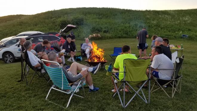Eric Brief and fellow teammates sit around the campfire enjoying post-game socializing.
